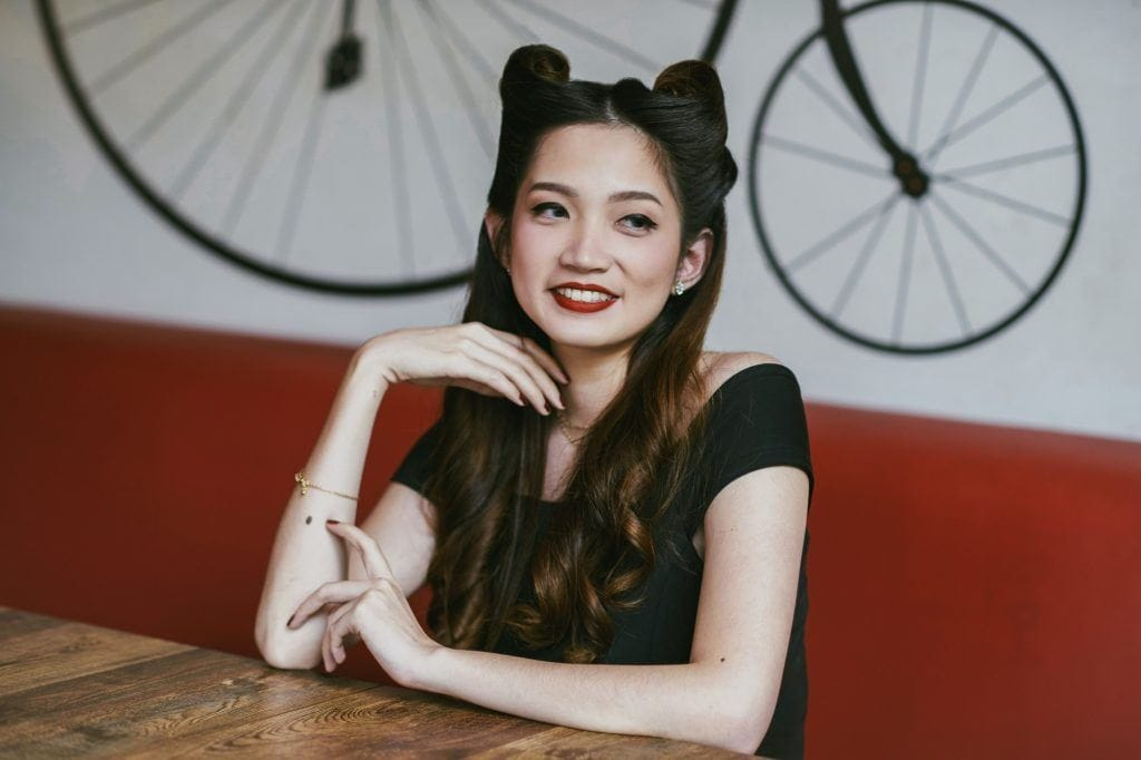 Asian woman with victory rolls hairstyle as Halloween glam