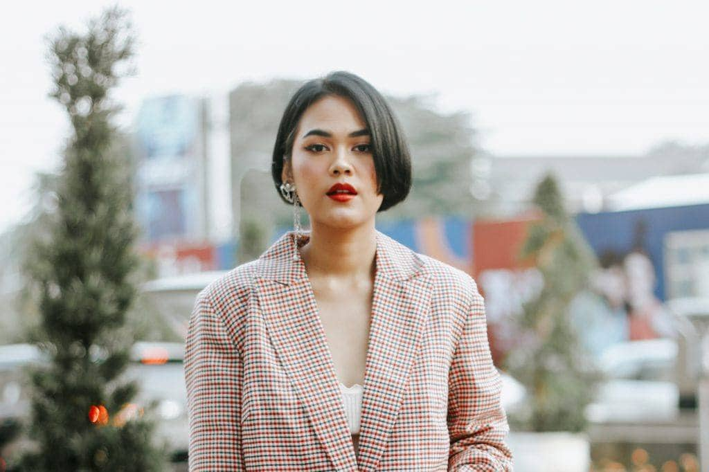 Asian woman with short straight hair wearing a beige jacket
