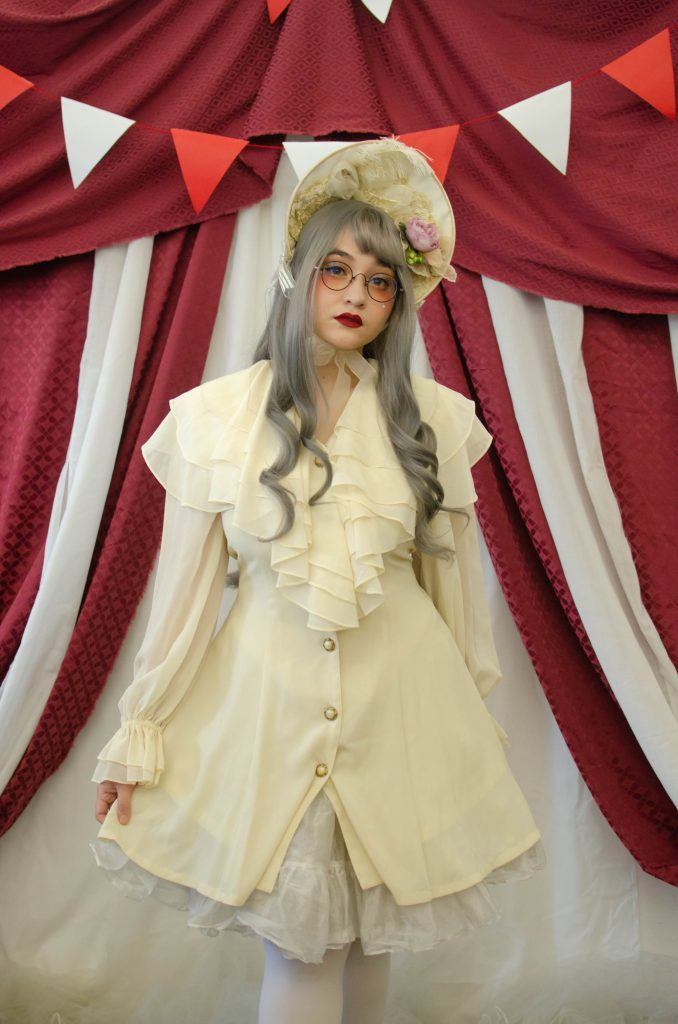 Asian woman with long gray wearing a while doll costume