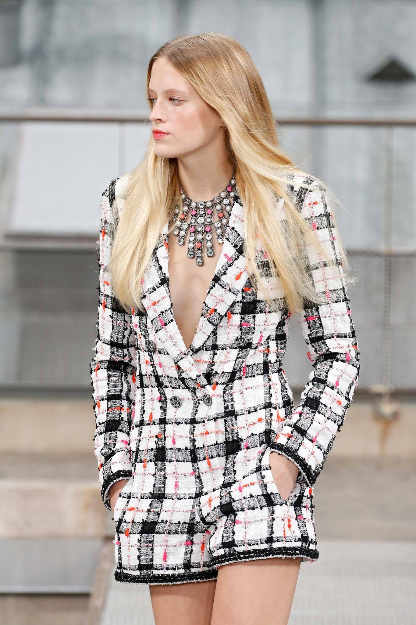 Caucasian woman with long blonde ombre hair wearing a plaid long-sleeved outfit on the runway