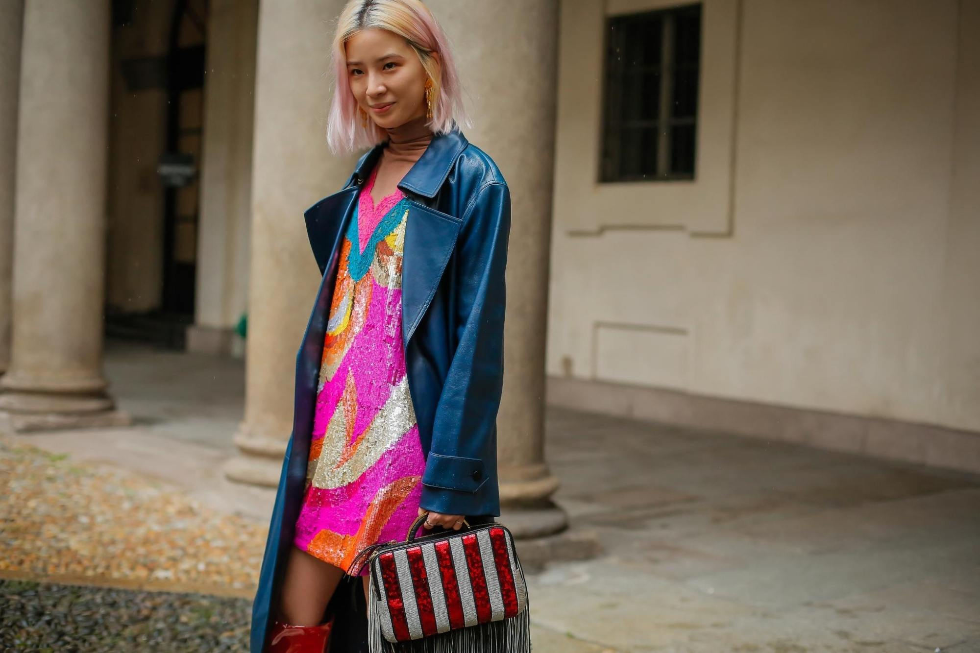 Asian woman with short blonde hair wearing a blue coat and pink dress outdoors