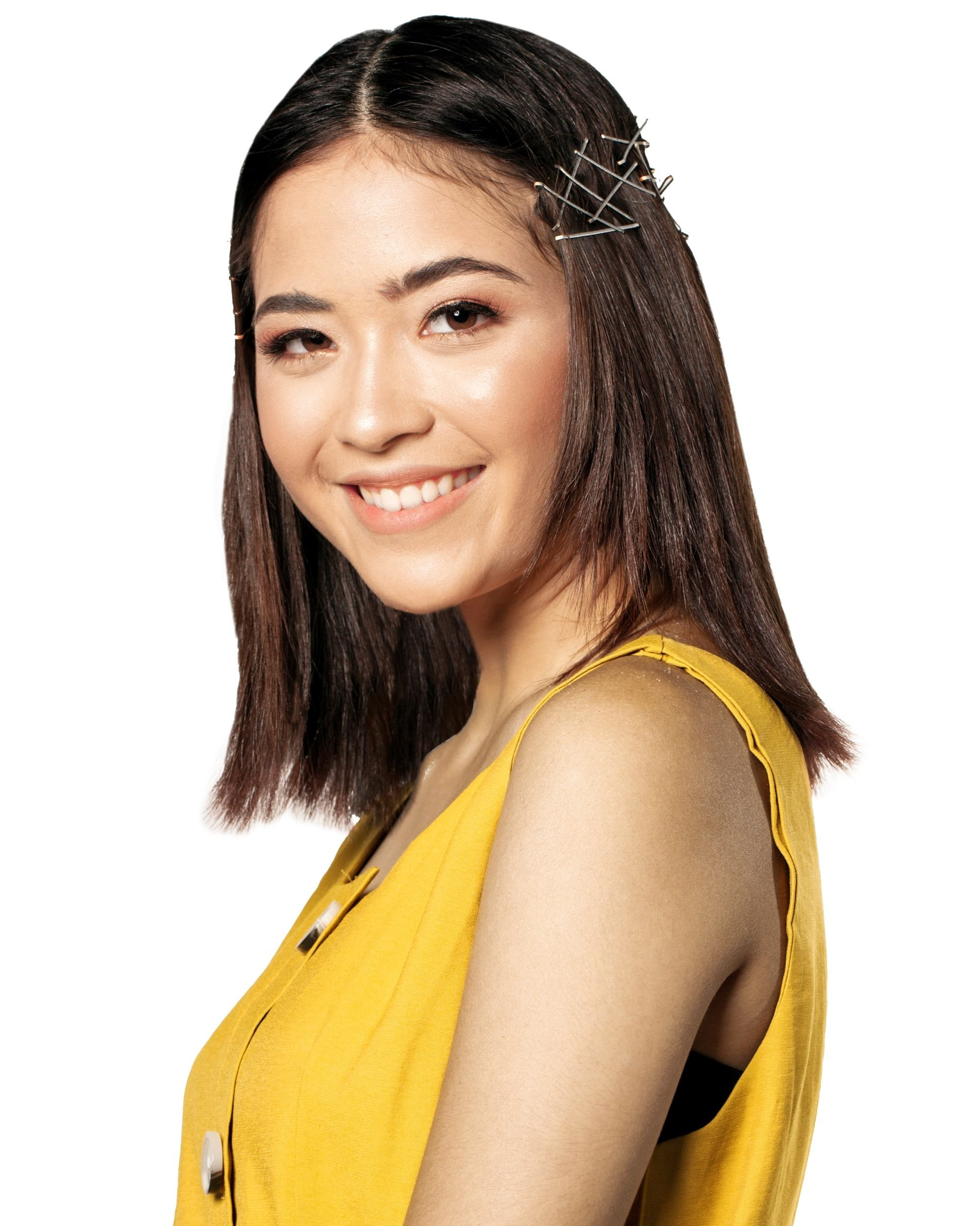 Asian woman with hair in bobby pin hair crown wearing a sleeveless yellow top