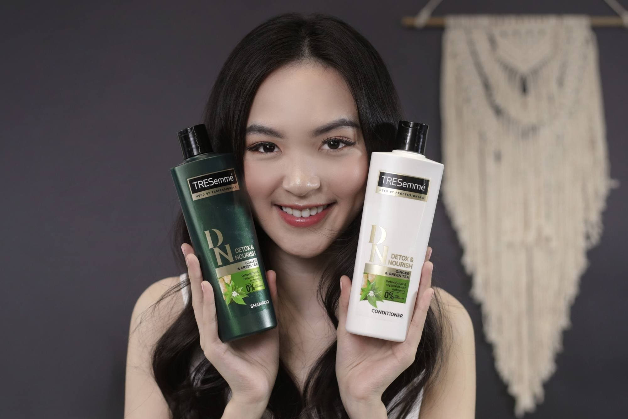Asian woman with long black hair holding shampoo and conditioner bottles smiling