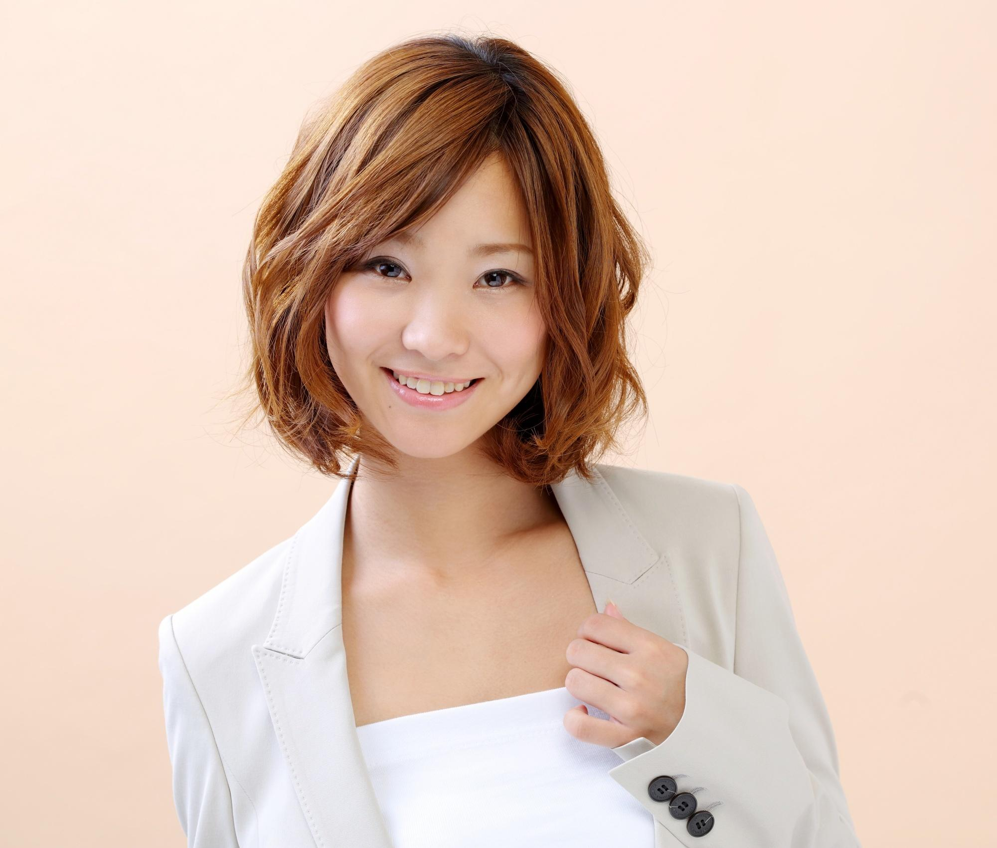 Asian woman with short brown wavy hair wearing a blazer and smiling
