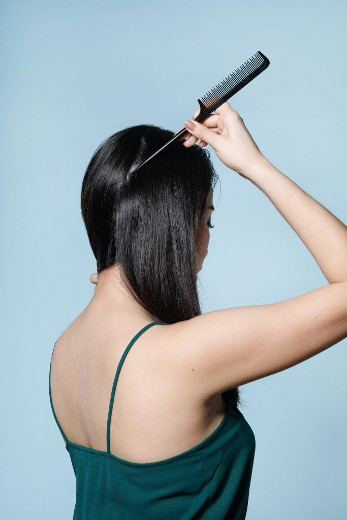Back shot of an Asian woman parting her hair into sections using the tip of a tail comb