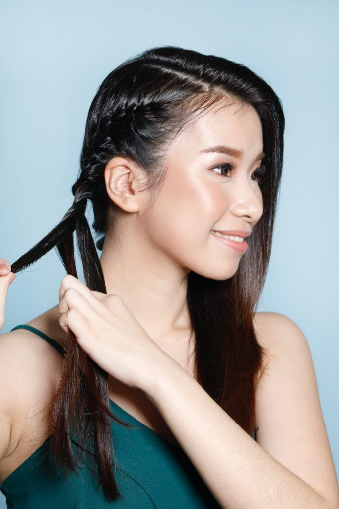 Asian woman braiding her hair