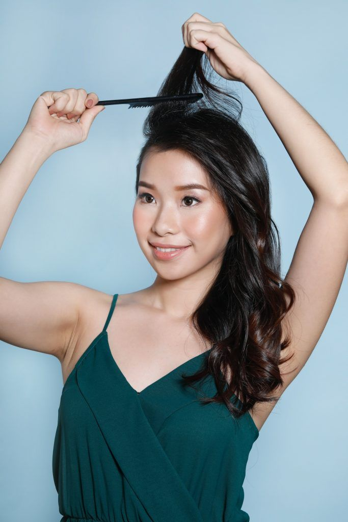 Side braid with voluminous waves: Asian woman teasing her hair with a comb