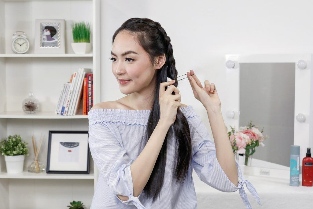 Asian woman tying her side-swept Dutch braid with an elastic