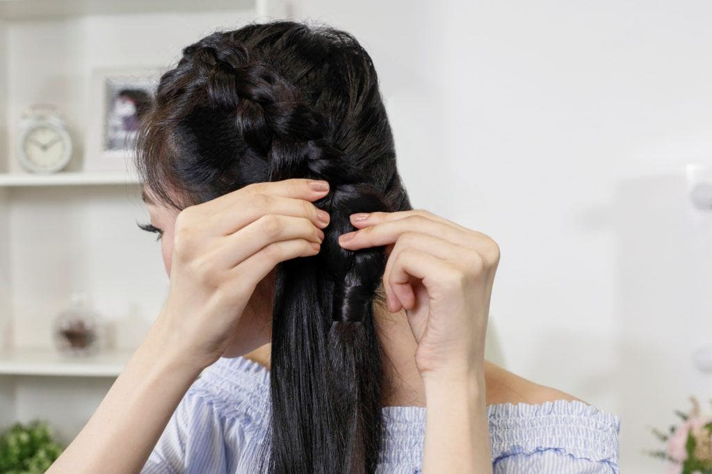Asian woman making her Dutch braid look wider