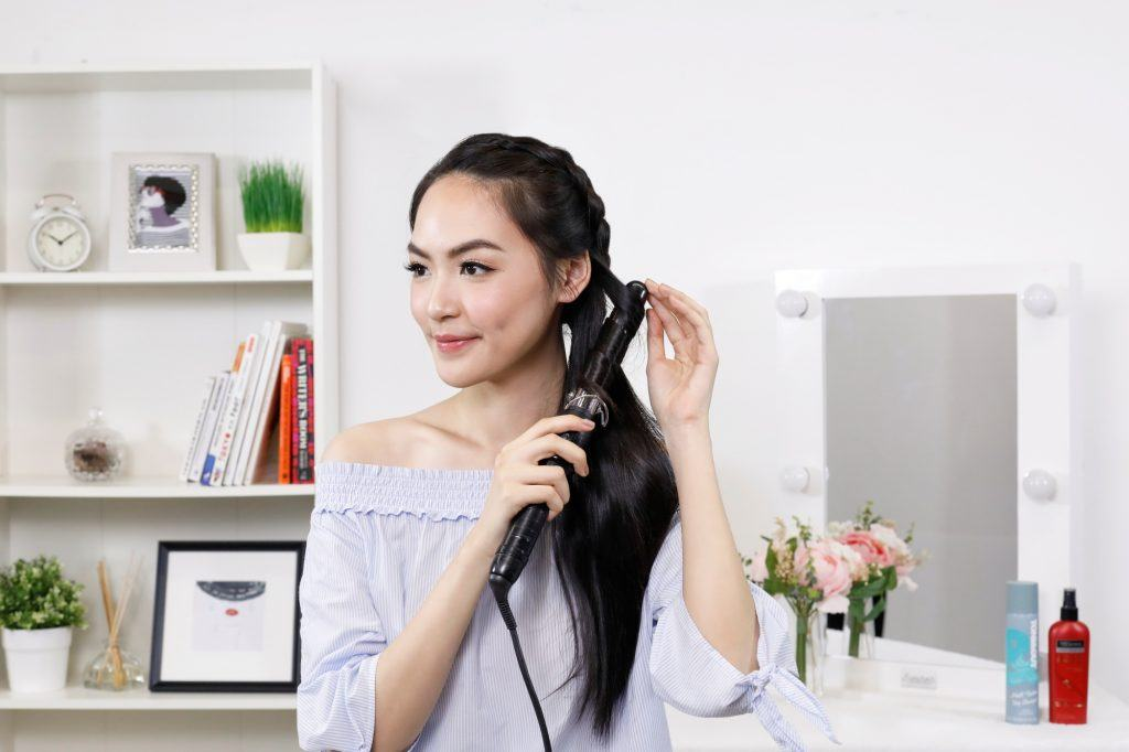 Asian woman curling her hair with a curling iron