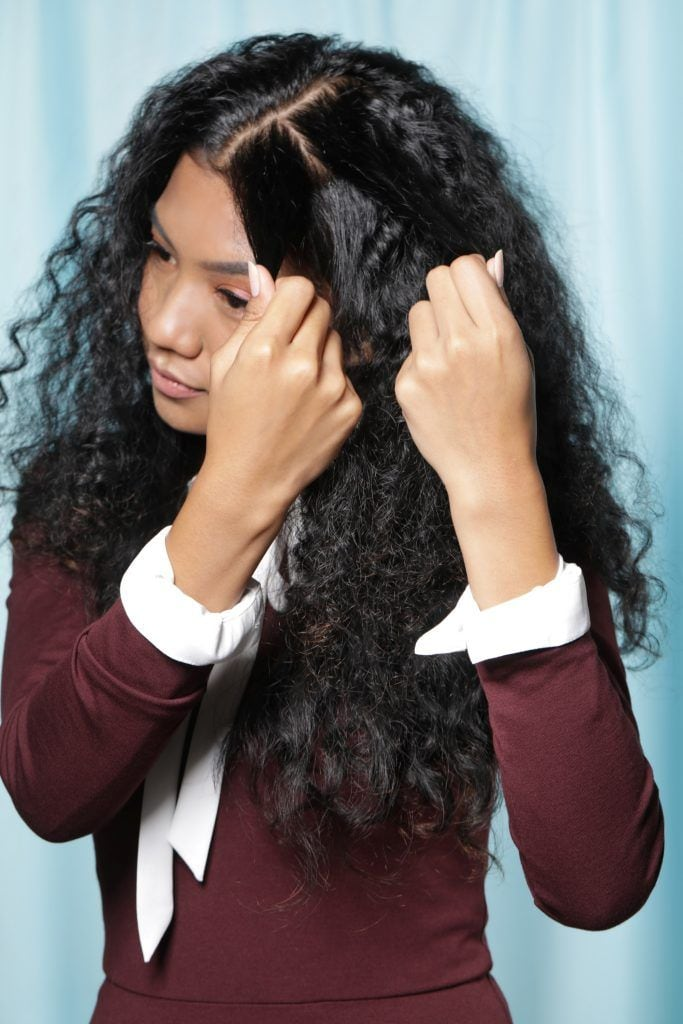 Asian woman with long hair hair holding a small section of her hair