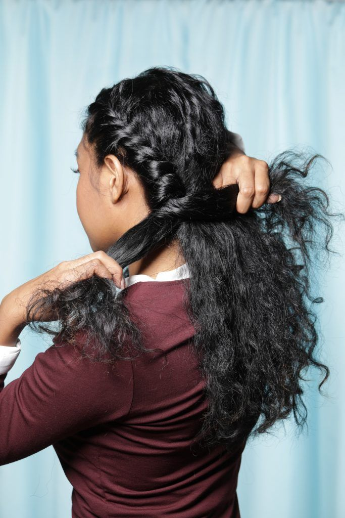 Back shot of an Asian woman twisting a section of her curly hair