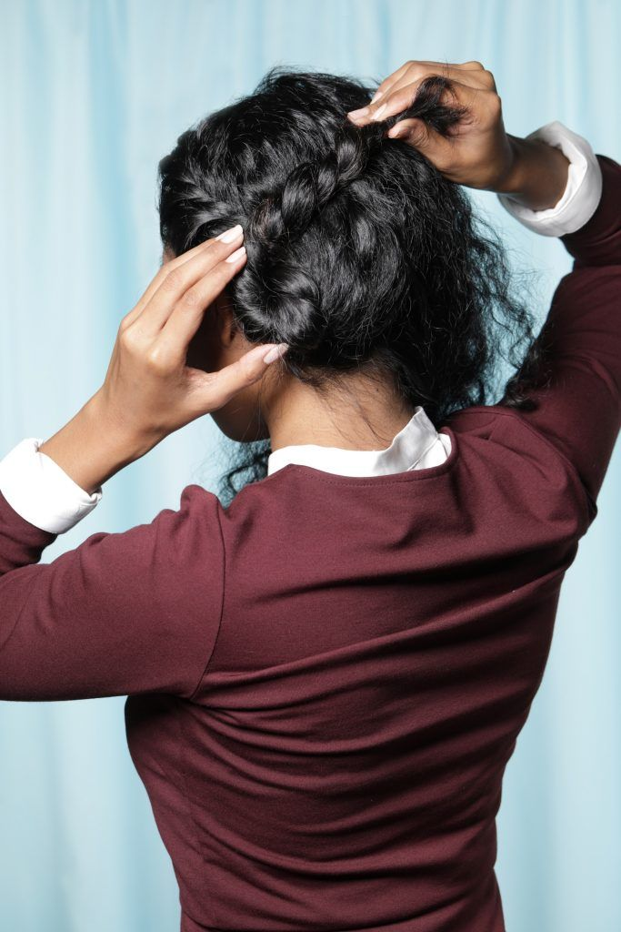 back shot of an Asian woman creating a bun shape with her hair near her nape