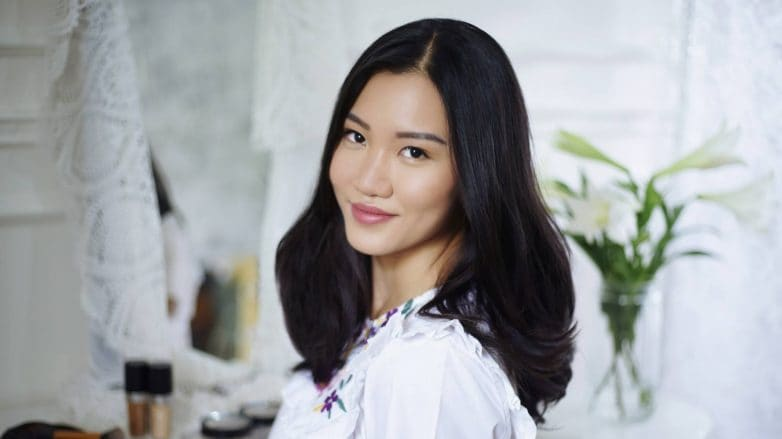 Asian woman with shiny hair wearing a white blouse