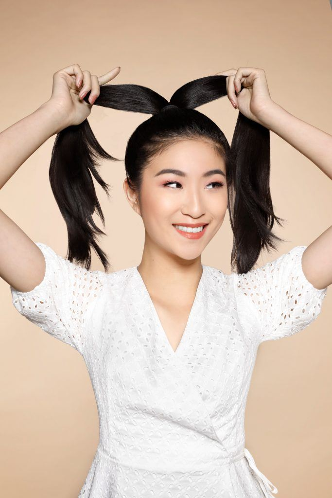 girl wearing a white top is smiling while dividing her ponytail into two sections