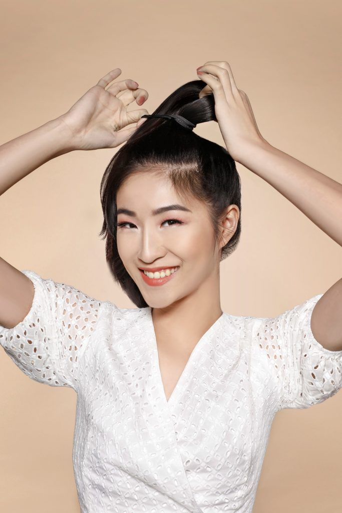 Asian girl wearing a white top is tying her hair into a ponytail for one of the easy hairstyles for women