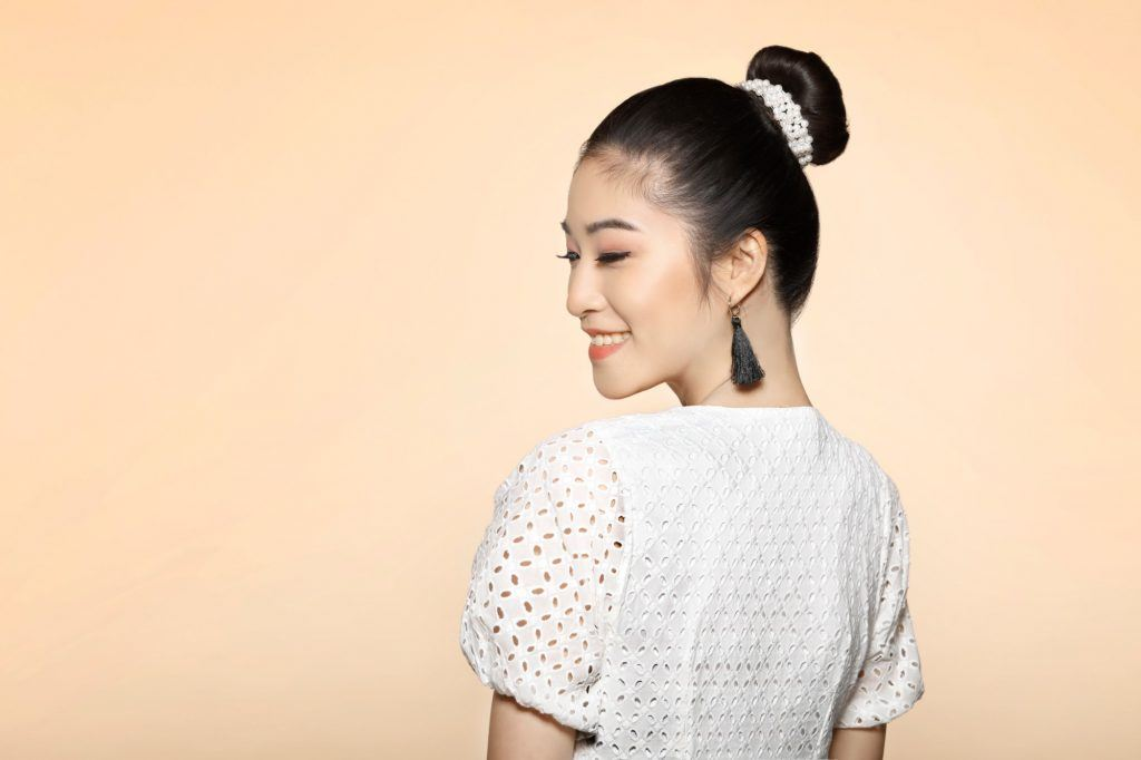 girl wearing a white top and dangling earrings with her hair in a bun which is one of the easy hairstyles for women