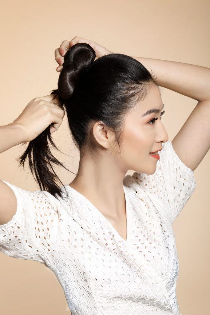 girl wearing a white top is making a bun to achieve one of the easy hairstyles for women