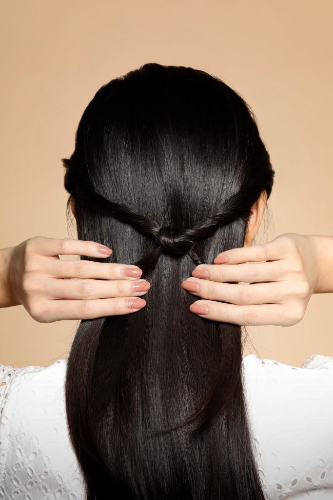 back of girl's head is seen with the girl forming a knot in her hair
