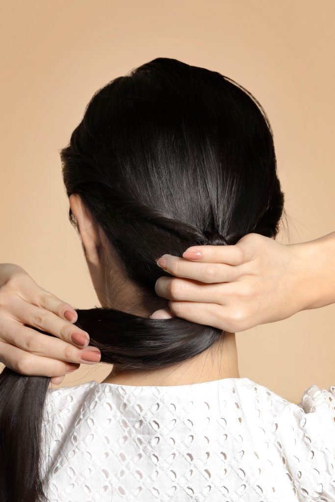 back of girl is seen, with her making a low ponytail for one of the easy hairstyles for women