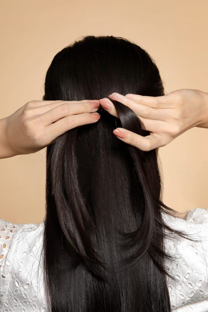 back of girl's head is shown with her hands tying her hair