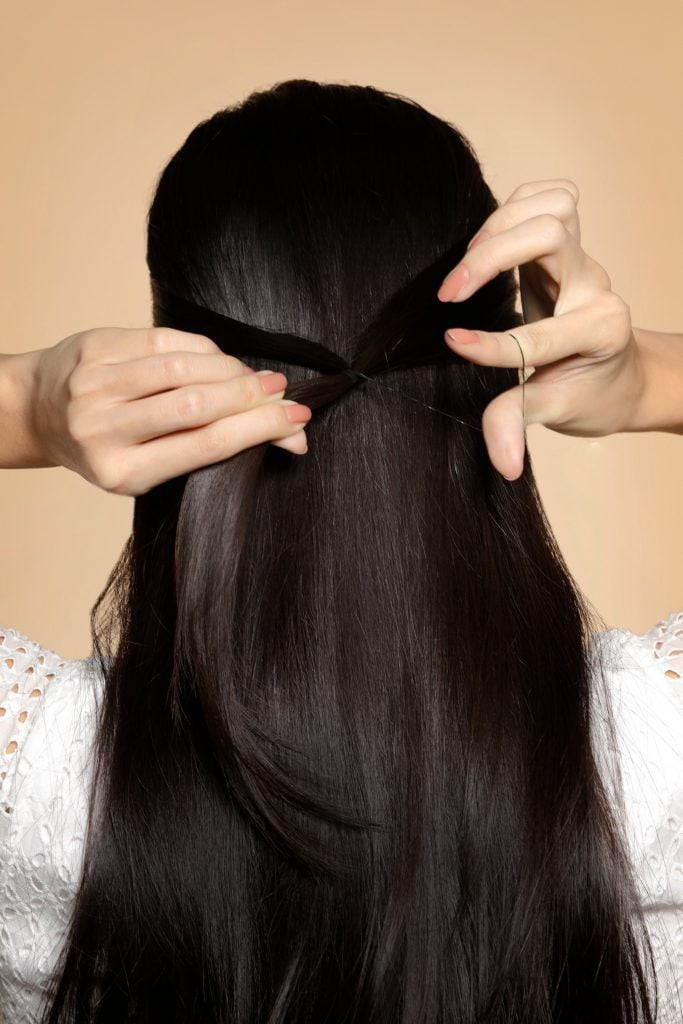 back of girl is showing her tying her hair for one of the easy hairstyles for women