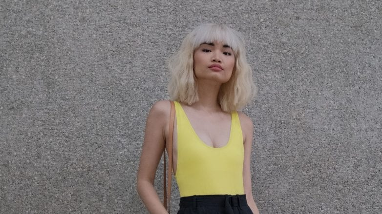 Color Fading: Asian woman with short blonde hair wearing a neon yellow top