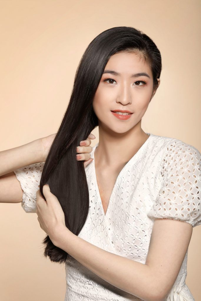 girl wearing a white top is holding her long black hair to prepare it for one of the easy hairstyles for women