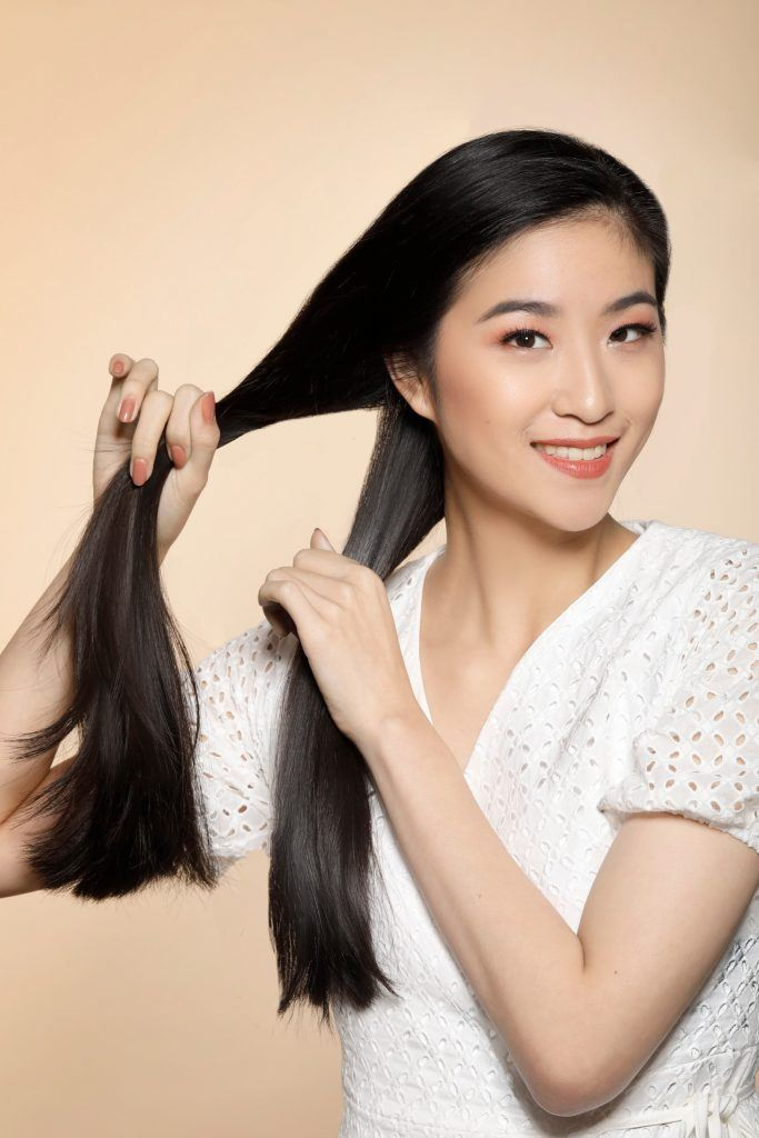 girl wearing a white top is preparing her hair for one of the easy hairstyles for women