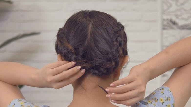 Back shot of Asian woman pinning her milkmaid braid for short hair