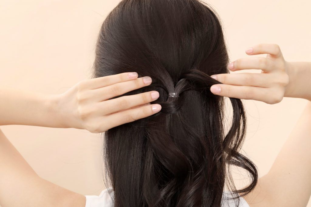 Asian woman creating a knot on her half up bridesmaid hairstyle