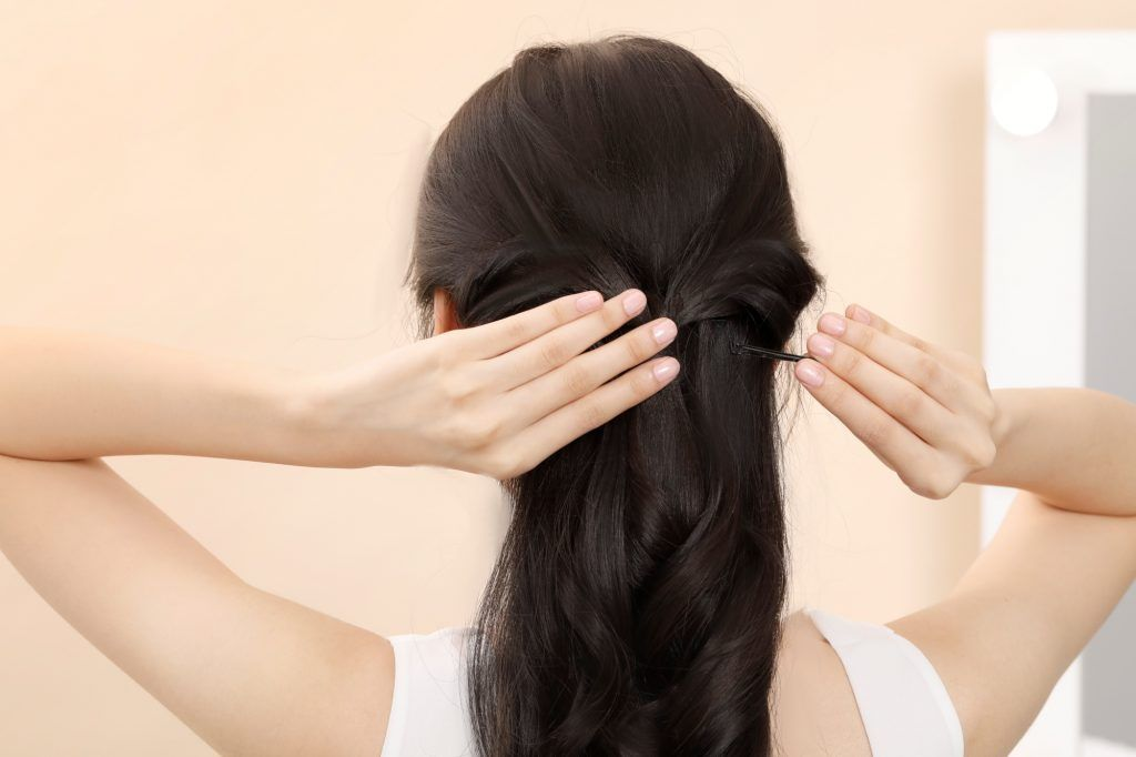 Asian woman pinning her half up bridesmaid hairstyle