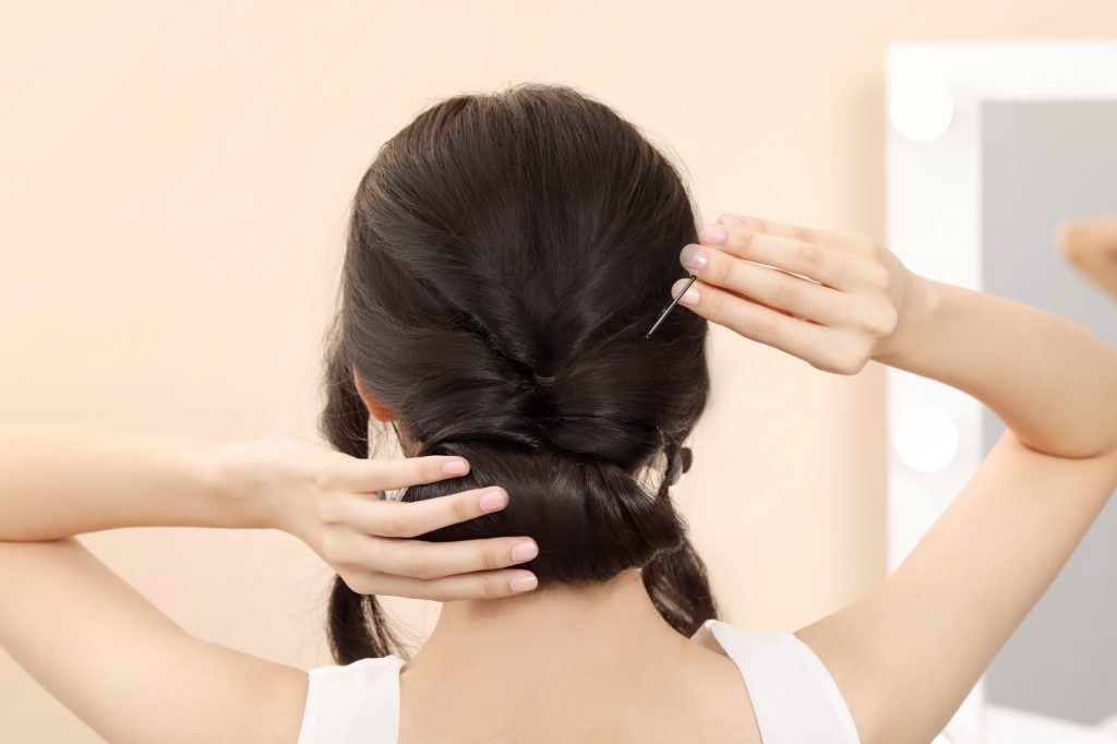 Asian woman creating a deconstructed chignon