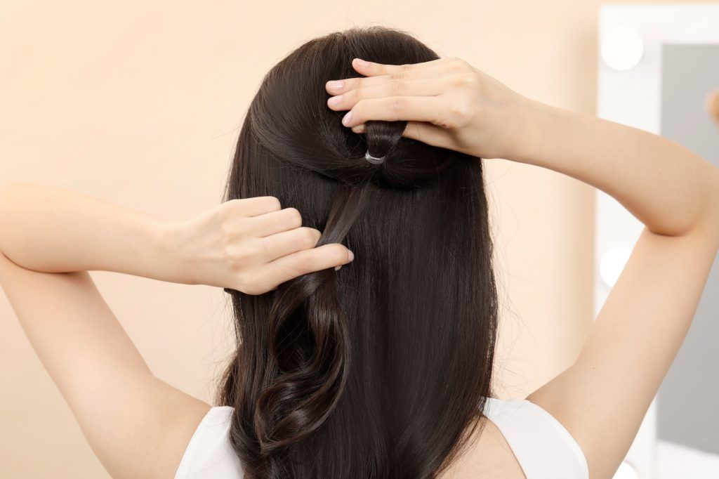 Asian woman creating a loose ponytail on her crown