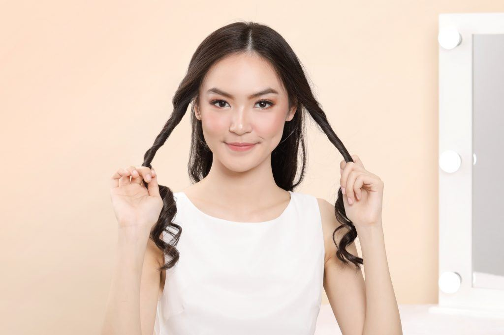 Asian woman twisting sections of hair