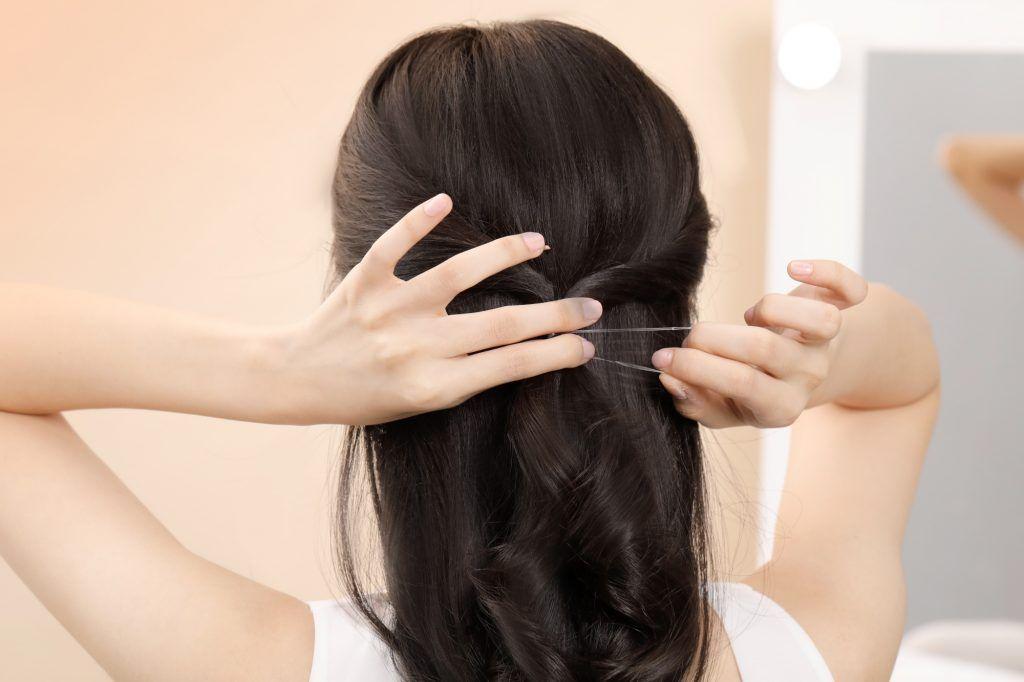 Back shot of an Asian woman tying a half updo