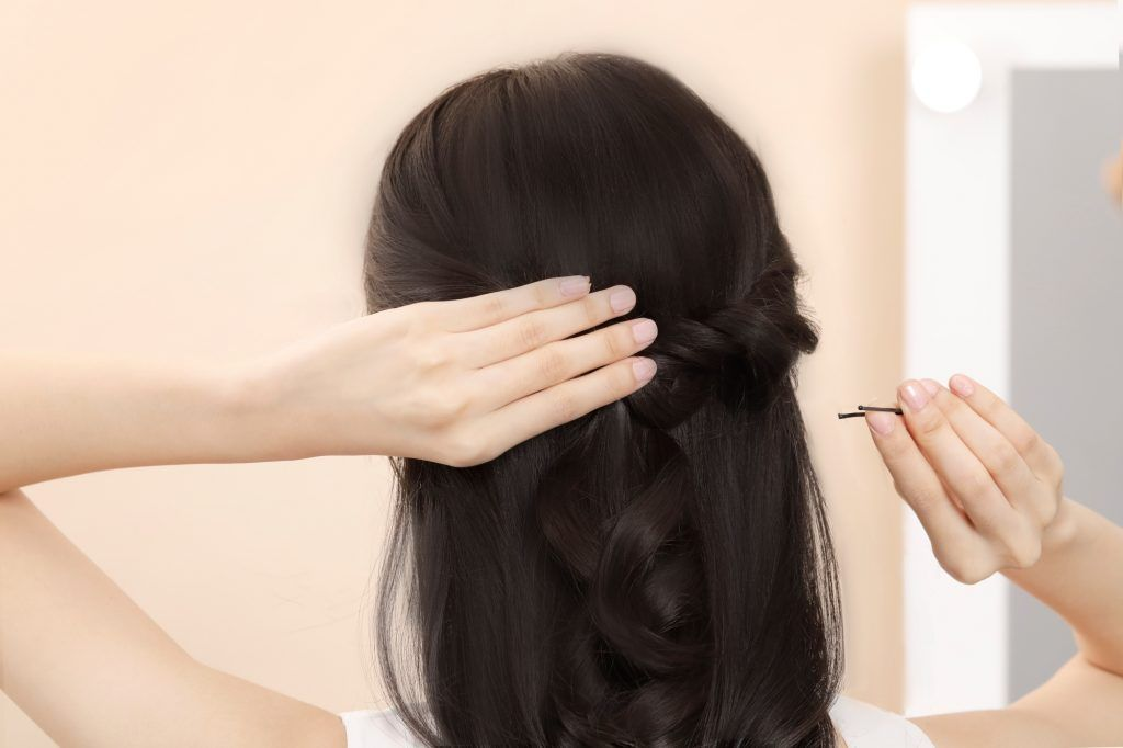 Asian woman creating a half up bridesmaid hairstyle