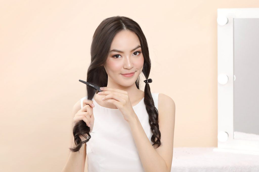 Asian woman clipping sections of her hair