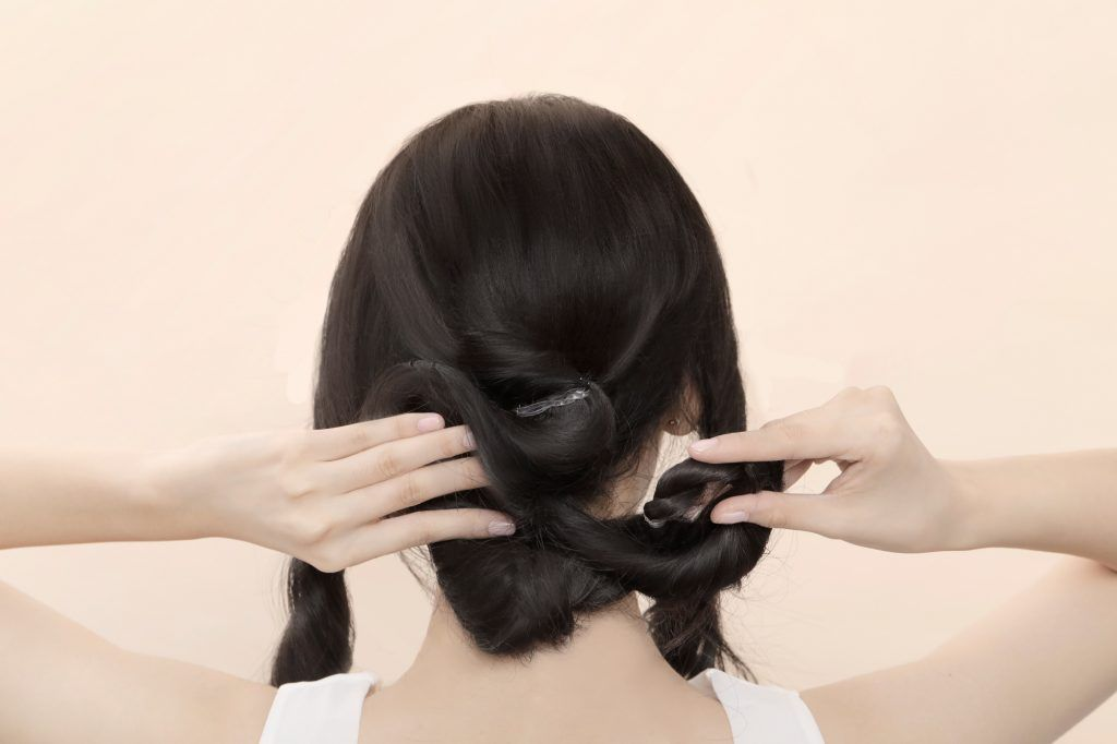 Asian woman creating a twisted rope bun bridesmaid hairstyle