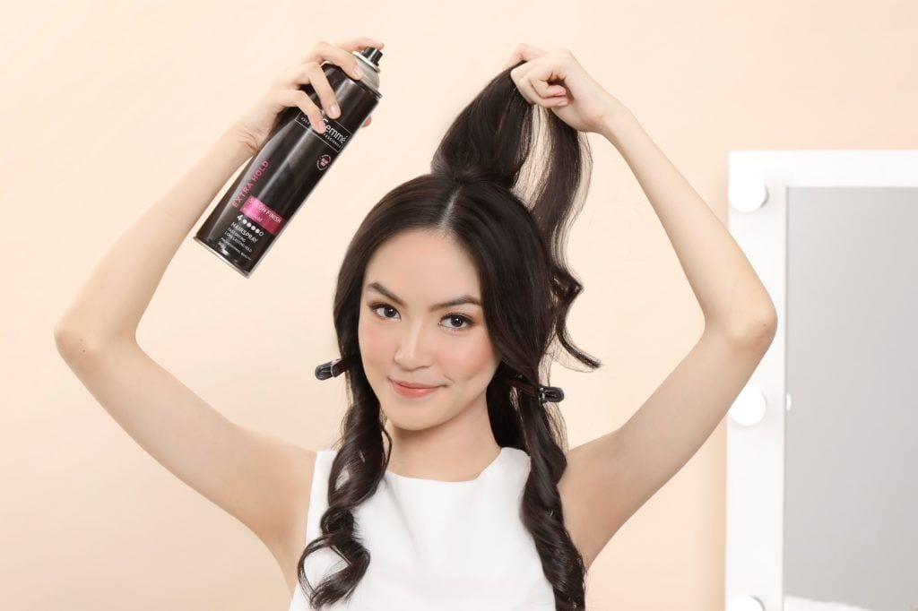Asian woman spraying hairspray on a section of her hair