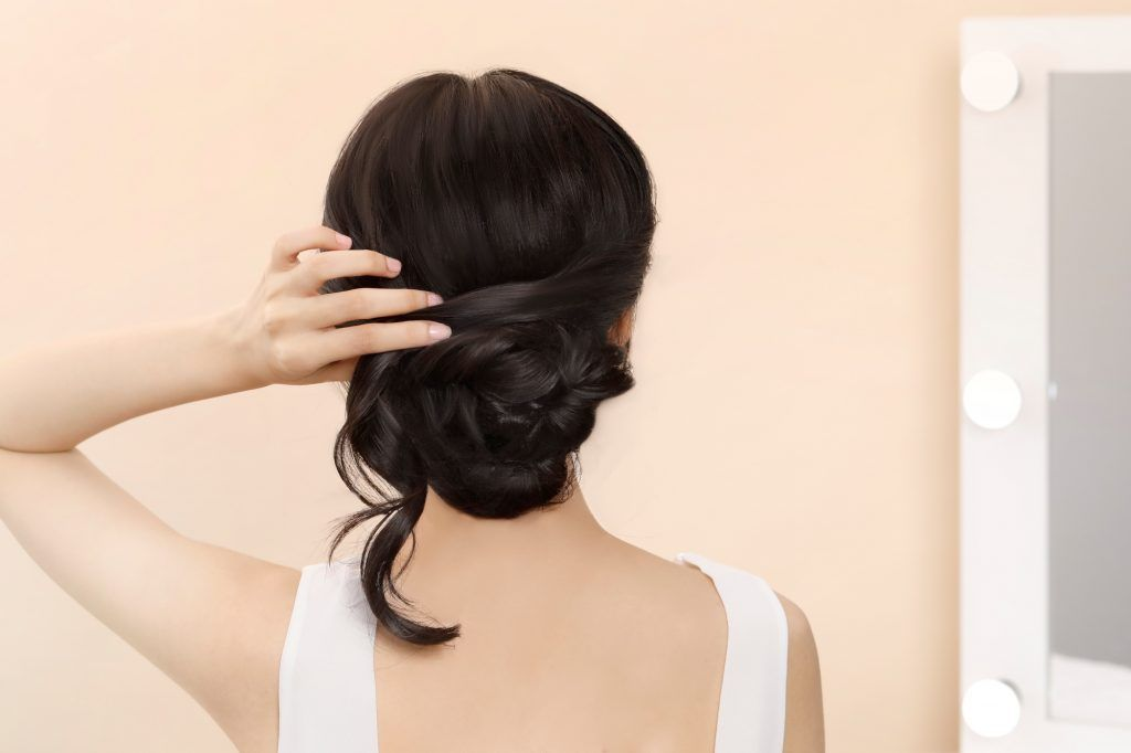 Asian woman wrapping a section of hair around her bun