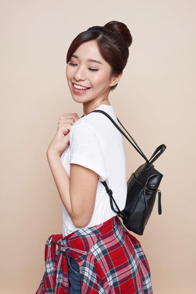 Asian woman with a hair donut wearing a white shirt carrying a black leather backpack