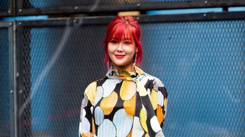 Woman with short red hair with bangs wearing a printed dress outdoors