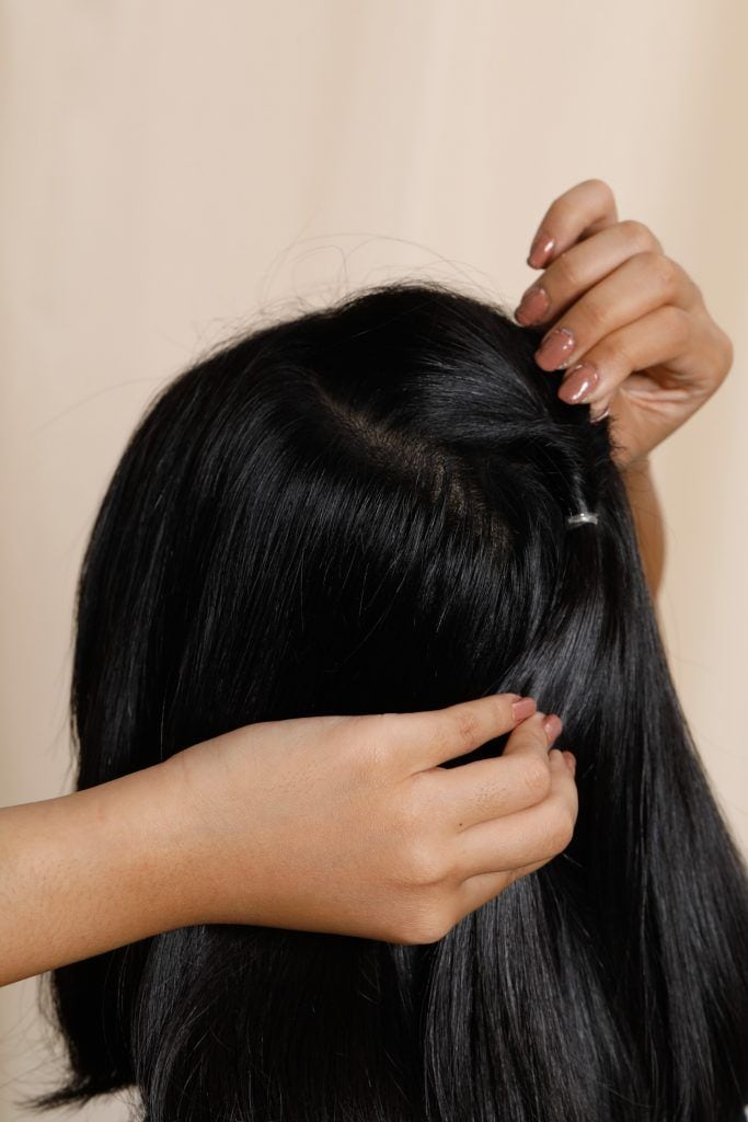 Girl is showing how she is creating a hole on her ponytail