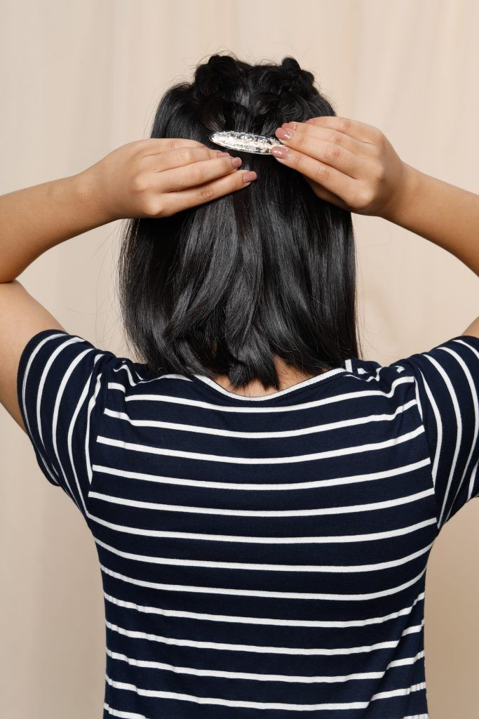 girl is showing how she puts on a hair accessory to complete one of the short hairstyles for round faces