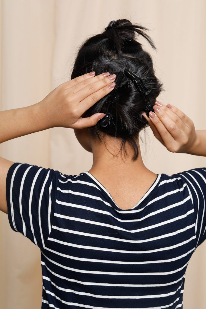 girl wearing a striped top is showing how she clips her hair for one of the short hairstyles for round faces