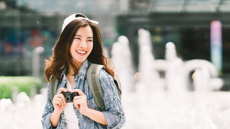 Asian woman with long hair wearing a cap and denim jacket outdoors