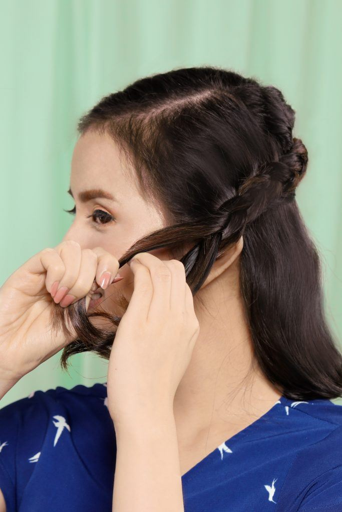 Asian woman creating a half up Dutch crown braid for short hair