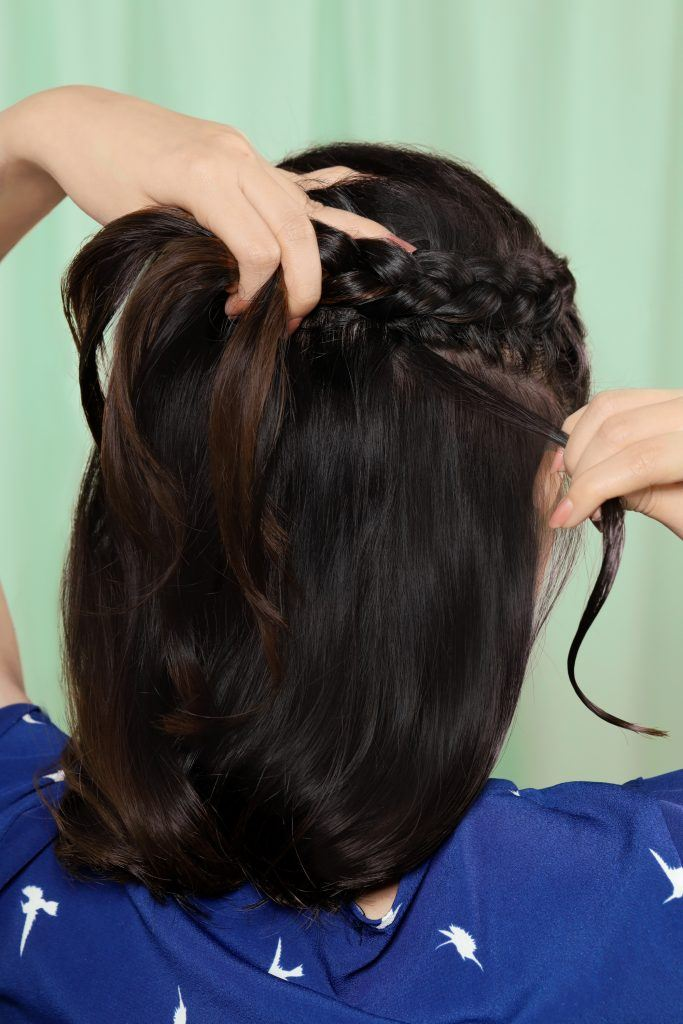 Back shot of an Asian woman making a half up Dutch crown braid for short hair