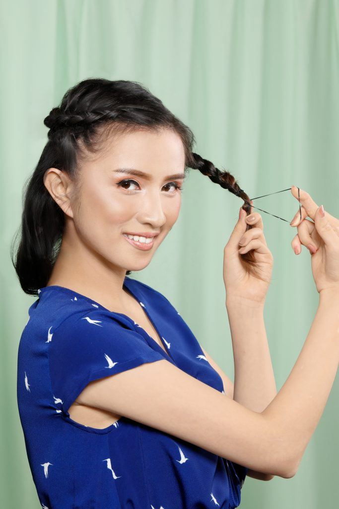 Asian woman tying the end of her braid